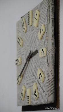 Customisez une horloge ikea à l'aide de carton, de peinture, de scotch double face, et papier journal et de dominos